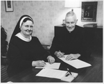 Mary Honora Kroger and Paul O'Connor signing documents by Keller Studio